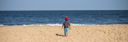A three year old boy looking out over the vast Atlantic Ocean.  It sort of makes you wonder what he is thinking about.  Photo was taken in Point Pleasant New Jersey. Stock Photo