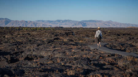 A woman walking in the lava fields of Craters of the Moon National Monument, Idaho, United States