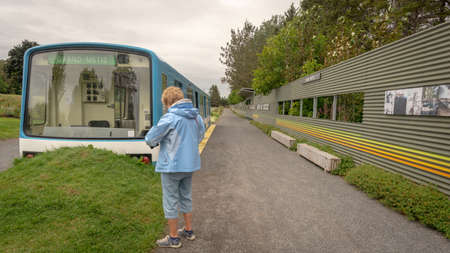 Metis-sur-Mer, Quebec, Canada - August 23, 2018: Old Montreal metro car installed at the entrance of the Reford gardens with an older woman looking at it, captured during an overcast summer day, Metis-sur-mer, Quebec Editorial