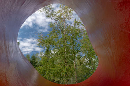 Metis-sur-Mer, Quebec, Canada - August 23, 2018:  View of a tree through a sculpture, Reford gardens, Metis-sur-mer, Quebec