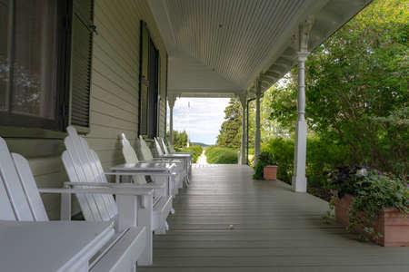 Metis-sur-Mer, Quebec, Canada - August 23, 2018: Front house veranda of the Estevan Lodge, with adirondack chairs, Reford gardens, Metis-sur-mer, Quebec Editorial