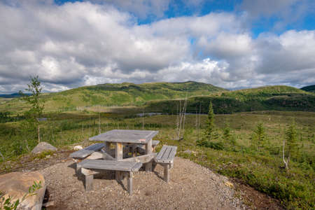 Picnic table set on a lookout over a taiga forest growing back after a wildfire in Les Grands-Jardins National Park, Province of Quebec, Canada