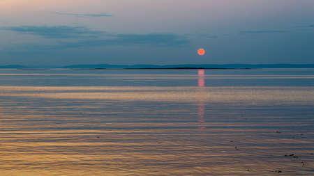 Orange sunset on the St. Lawrence River in summer time, Notre-Dame-des-Neiges, Province of Quebec, Canada Banque d'images