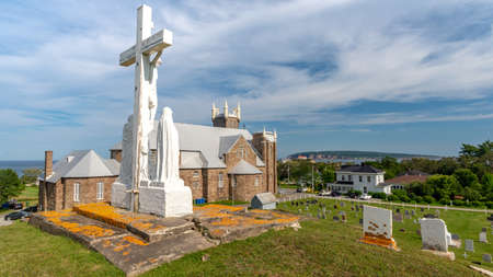 View on the back of St.Michel church with the cemetery and a cross in the foreground, Perce, Quebec, Canada