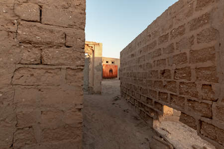 RAS AL KHAIMAH, UNITED ARAB EMIRATES - MARCH 8, 2019: A red dominance photograph at the end of a perspective in the abandoned village of Al Jazirah Al Hamra at sunset, Emirate of Ras Al Khaimah Editorial