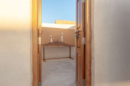 RAS AL KHAIMAH, UNITED ARAB EMIRATES - MARCH 8, 2019: Door opening on a painting as part of an art exhibit in the abandoned village of Al Jazirah Al Hamra at sunset, Emirate of Ras Al Khaimah Editorial