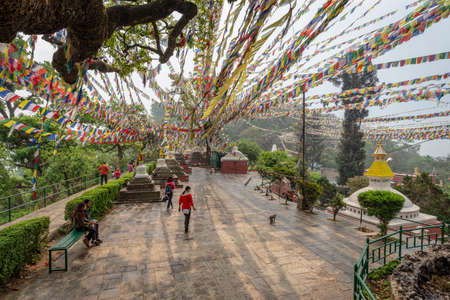Kathmandu, Nepal - March 30, 2019:  Few visitors and lines of prayer flags forming convergent lines with few sun rays during an overcast spring morning at the monkey temple (Swayambhunath temple) in Kathmandu Editöryel