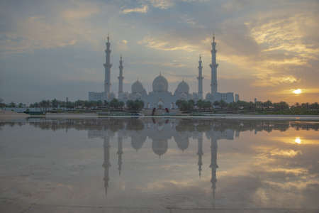 Axial view of the Great Mosque of Abu Dhabi at sunset with reflection over a water mirror with nobody, United Arab Emirate