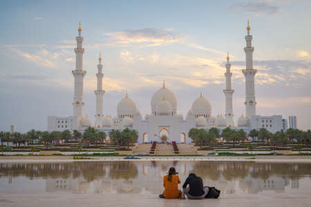Axial view of the Great Mosque of Abu Dhabi at sunset with reflection over a water mirror with a couple seen from behind, United Arab Emirate