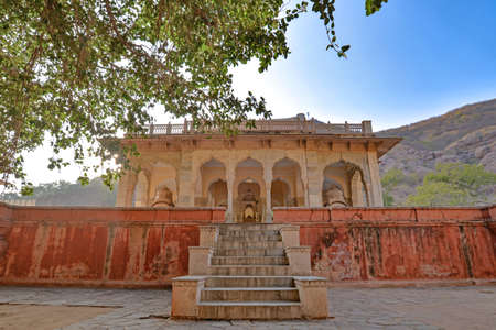 Pink and yellow cenotaph with hill backdrop, at the Royal Gaitor, Jaipur, Rajasthan, India