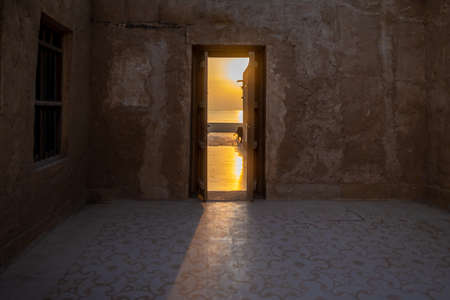 Courtyard door opening on a seafront promenade. Taken early morning in the old souk of Al Wakrah, Qatar