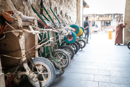 Doha, Qatar - 25 Nov 2016: Row of wheelbarrows waiting for their porter in the early afternoon, with 2 men in the background. Taken in Souq Wakif, Doha