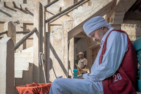 Doha, Qatar - 3 Dec 2016: A porter is waiting for his shift to start, while another souk employee is passing by. Taken in Souq Wakif, Doha