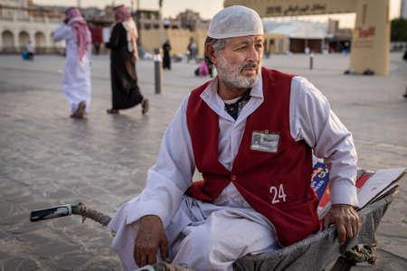 Doha, Qatar - 17 Dec 2016: A man porter is waiting for his next customer while seating on a wheelbarrow. Taken in Souq Wakif, Doha