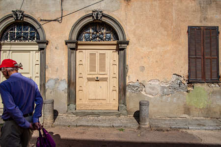 Porto-Vecchio, Corsica, France - Sep 20, 2019: Male tourist passing by an ornate doorway  Taken during a summer afternoon. 新聞圖片