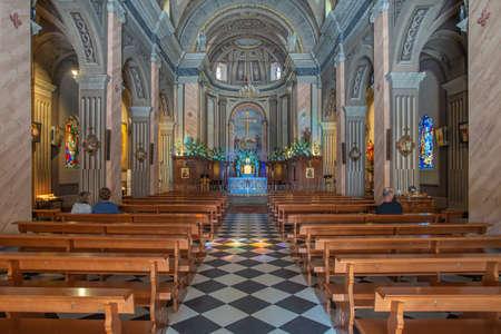 Porto-Vecchio, Corsica, France - Sep 20, 2019: Three persons seating inside the St. John the Baptist church.