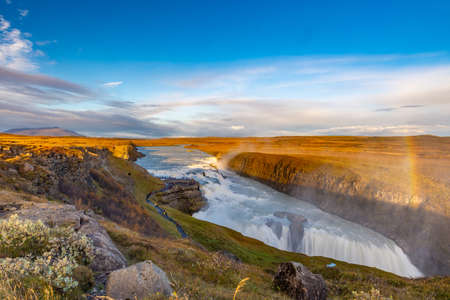 Gullfoss waterfall seen from afar with unrecognisable visitors, taken on with clear sky at the end of an early October afternoon, Iceland
