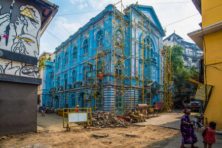 Mumbai, India - December 15, 2017: A blue heritage building being renovated with scaffoldings with some passersby.