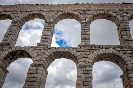 Detail view of the Segovia roman aqueduct with partly overcast sky in the background, Spain