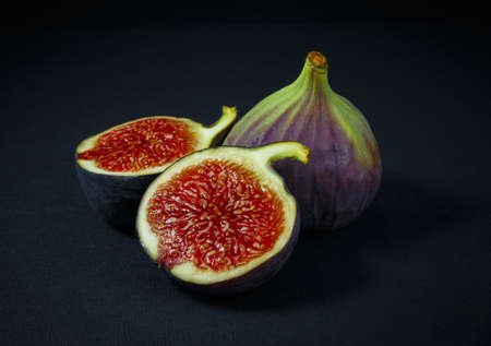 figs, whole and half on green wooden background 版權商用圖片