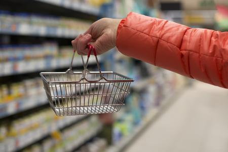 Woman hold basket in supermarket. Shelfs on background. Zdjęcie Seryjne
