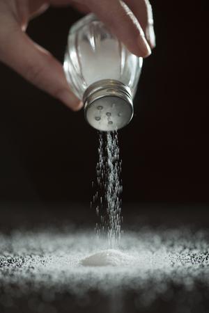 Adding salt. Backlight to salt from salt shaker. Close up