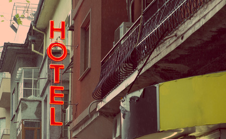 Small cheap hotel. Text Hotel on facade. Hotel in the city. Banque d'images