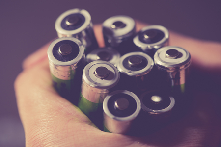 Hand hold many batteries. Close up