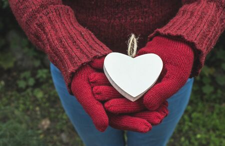 Hands in gloves and white heart shape Stock Photo
