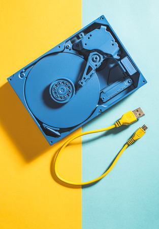 Blue colour hard disc and yellow USB cable Stock Photo