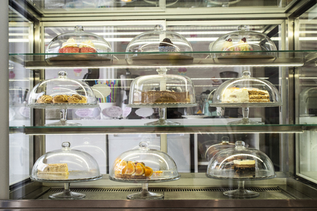 Pastries and cakes on showcase in the pastry shop. Glass lid Stock Photo