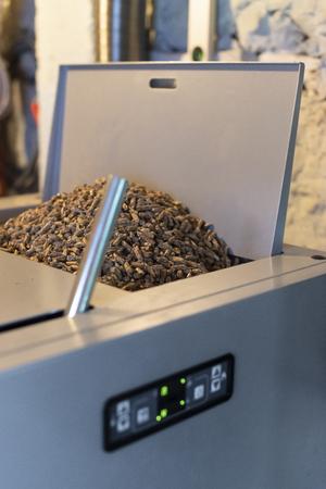 Heating boiler uses pellets as fuel. Pile pellets in the heater.