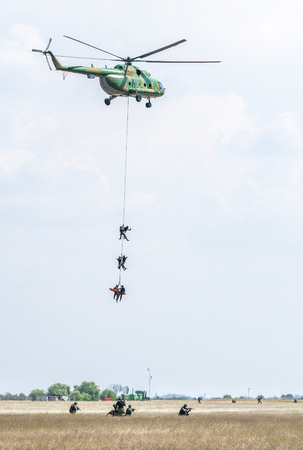 Soldiers go down a rope from military helicopter. Military special operation. 스톡 콘텐츠