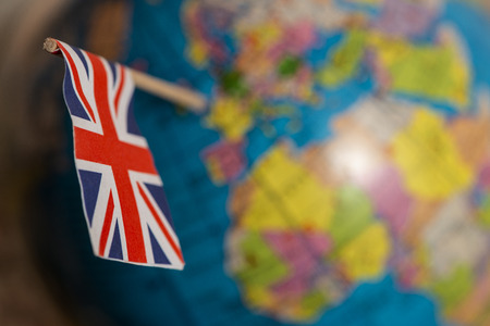 British flag on the world map. UK flag pricked on the globe points to the United Kingdom.