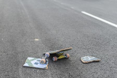 Broken skateboard on dark asphalt street. White street line. 免版税图像