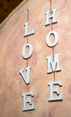 Love Home text on pink wall at home interior. White wooden charcters L O V E  and H O M E hooked with rope on wall. Concept of love and home.