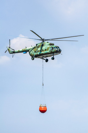 Green firefighting helicopter transporting water. Helicopter extinguishes fires.