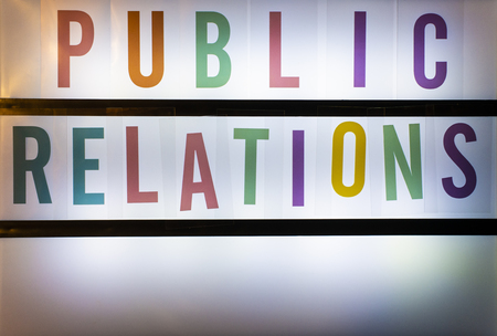 Public Relations text on backlight board. Colored Characters on white backlight background. Public relations concept.
