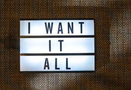 Message I want It All on illuminated board. Requests and wishes concept with text. Daylight from window. Room interior. Black letters Want it all. Reklamní fotografie