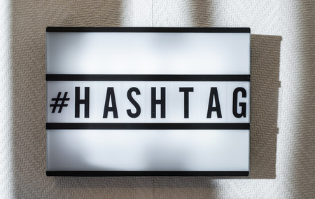 Message #Hashtag on illuminated board. Identify message concept with text. Daylight from window. Room interior. Black letters hashtag on white wallpaper wall.