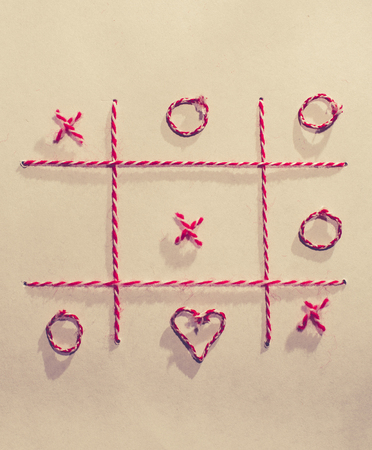 Tic-tac-toe game made of yarn on white paper sheet. Valentines day concept with tic tac toy symbols. Red and white colour xo symbols and heart shape. Stok Fotoğraf