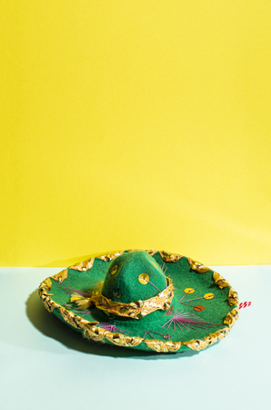 Mexican sombrero hat on geometric yellow and green pastel tone background. Green hat with mexican ornaments and decorations.