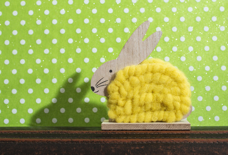 Yellow easter bunny in front of wall of points in a room. Bunny decoration and green wallpaper background on dots. Shadow of rabbit on the wall. Wooden bunny figure shape and yellow yarn. Minimalist concept.