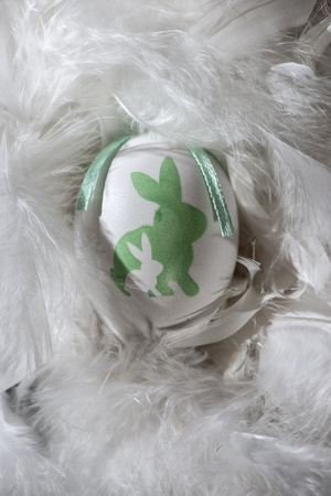 Green and white eggs on feather background. Easter conception with shape of rabbits on eggs. Stock Photo