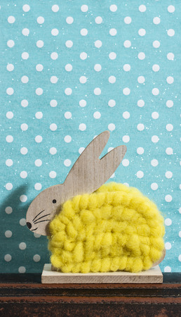 Yellow easter bunny in front of wall of points in a room. Bunny decoration and blue wallpaper background on dots. Shadow of rabbit on the wall. Wooden bunny figure shape and yellow yarn. Minimalist concept.