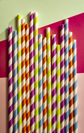 Colorful variegated drinking straws. Background of patterned straws and bright colour paper. Arranged straws next to each other. Concept for Summer time and drinking. Geometric backdrop.