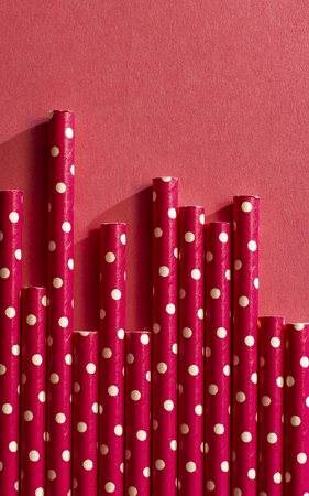 Red drinking straws on white points. Background of straws and bright colour paper. Arranged straws next to each other. Concept for Summer time and drinking. Geometric backdrop. Stock Photo