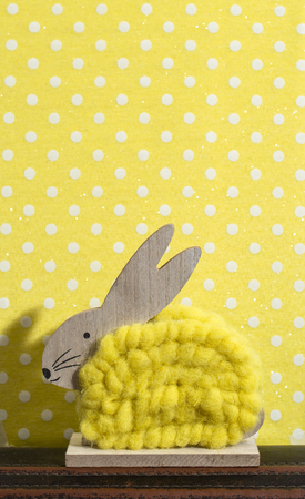 Yellow easter bunny in front of wall of points in a room. Bunny decoration and yellow wallpaper background on dots. Shadow of rabbit on the wall. Wooden bunny figure shape and yellow yarn. Minimalist concept.