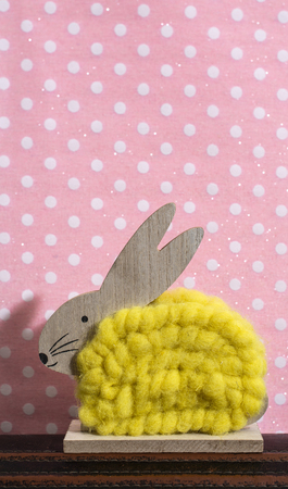 Yellow easter bunny in front of wall of points in a room. Bunny decoration and pink wallpaper background on dots. Shadow of rabbit on the wall. Wooden bunny figure shape and yellow yarn. Minimalist concept.