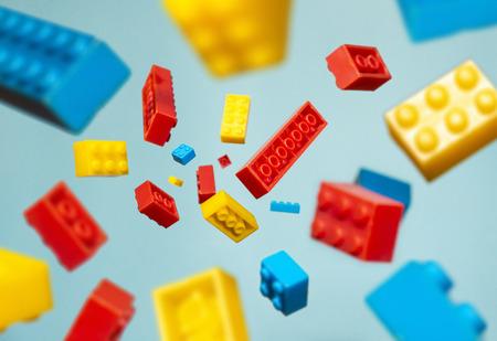 Geometrische Plastikwürfel in der Luft schweben. Konstruktionsspielzeug auf geometrischen Formen, die in Bewegung fallen. Blauer Pastellhintergrund. Kinderspielzeug. Kreisen Sie geometrische Formen auf Plastikziegeln ein.
